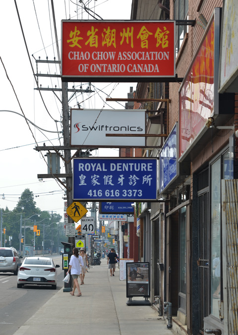 stores and signs on Dundas West near Augusta.  Chao Chow Association of Ontario, Swiftronics, Royal Denture, and others, some people walking on the sidewalk too