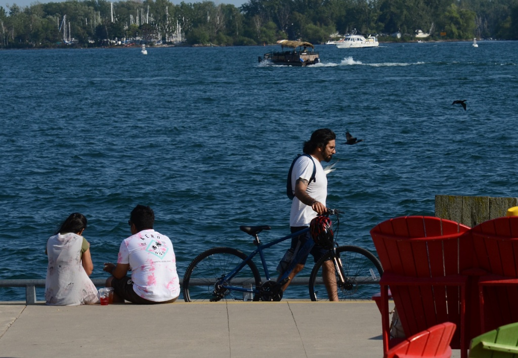 A couple sit with their backs to the camera on the edge of Lake Ontario while a male cyclist walks his bike past.  Two red Muskoka chairs in the picture as well as boats on the water