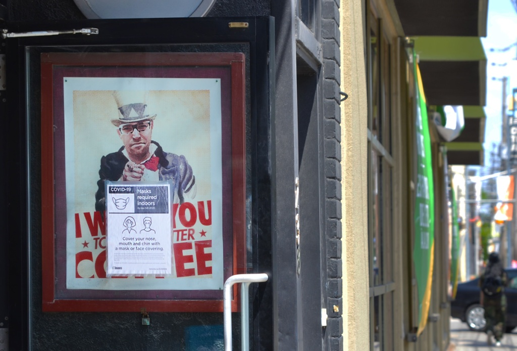 poster of a man, parody of uncle sam poster, top hat and pointing, words say I want you to like better coffee.  On the exterior of a door to a coffee shop, with covid mask notice in front of it