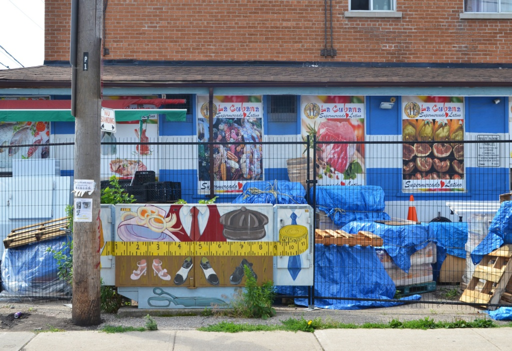 The side of La Cubana supermercado grocery store with pictures of food, also stored items under blue tarps, and a bell box painted with a yellow measuring tape and articles of clothing, a bonnet, a tie, a cap, and three pairs of shoes