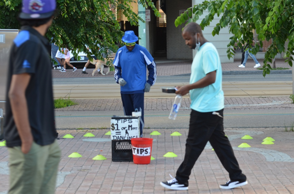 Two men walk past another man dressed in blue who dances for tips.  He's standing still because no one has given him any money