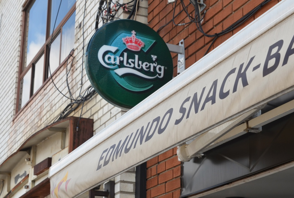 Awning cover on Edmundo Snack bar, with round Carlsberg beer advert above it, exterior