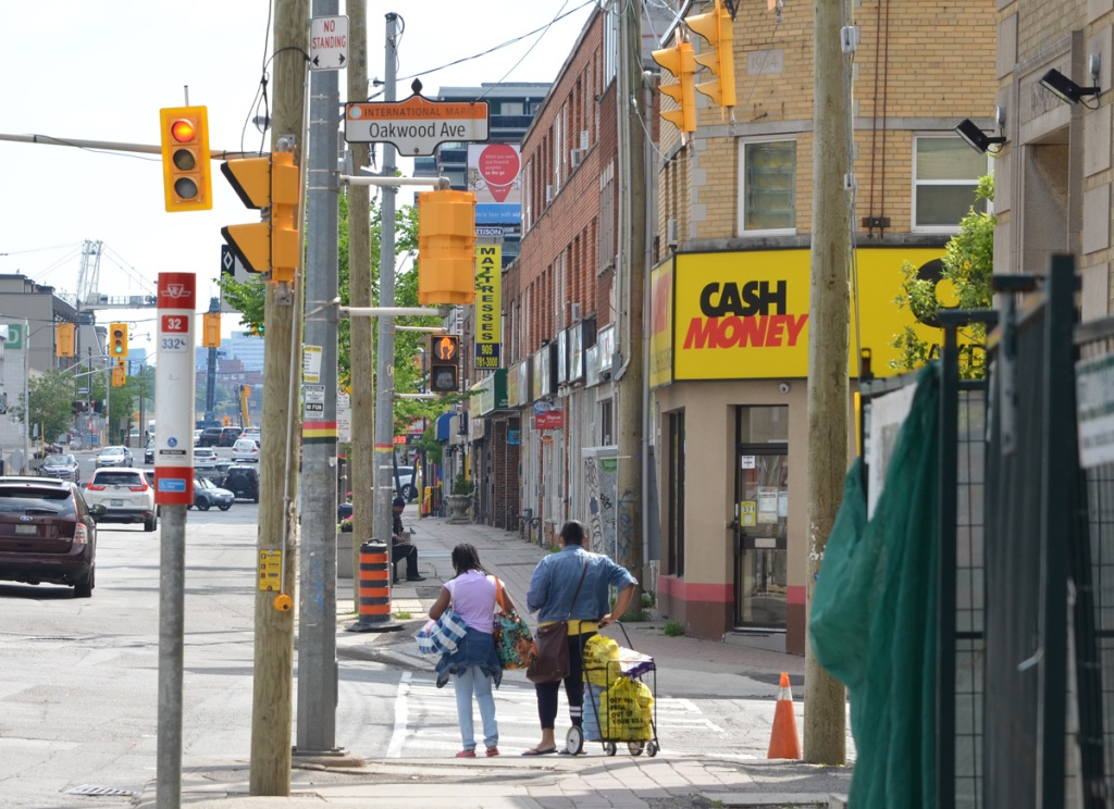 a mother and daughter stand with a shopping buggy waiting for a traffic light on Eglinton West at Oakwood, stores, traffic, man on bench on sidewalk