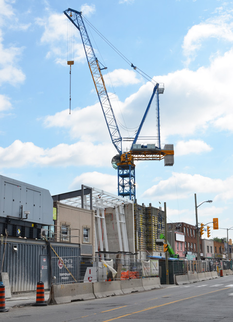 large blue crane above a construction site, building the new Oakwood Crosstown station on Eglinton West