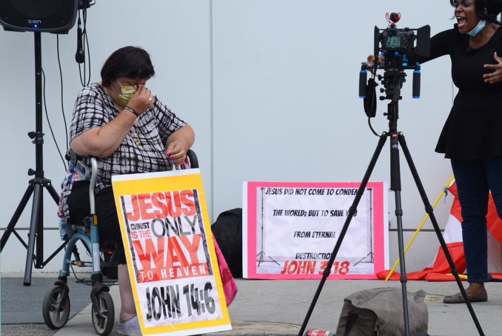 a black woman being video'd, a woman in a wheelchair with a sign leaning against her knees that says Jesus Christ is the only way to heaven John 14: 6  Sign at the back says Jesus did not come to condemn the world but to save it from eternal destruction.