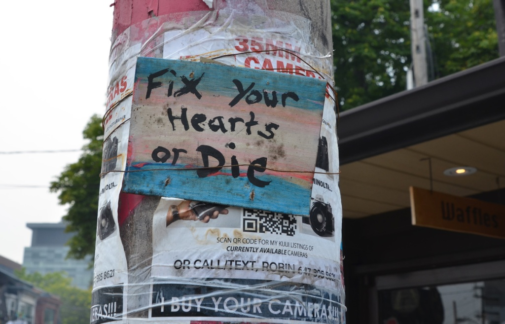 graffiti sign on a pole, covering an add for 35 mm cameras for sale, words that say fix your hearts or die