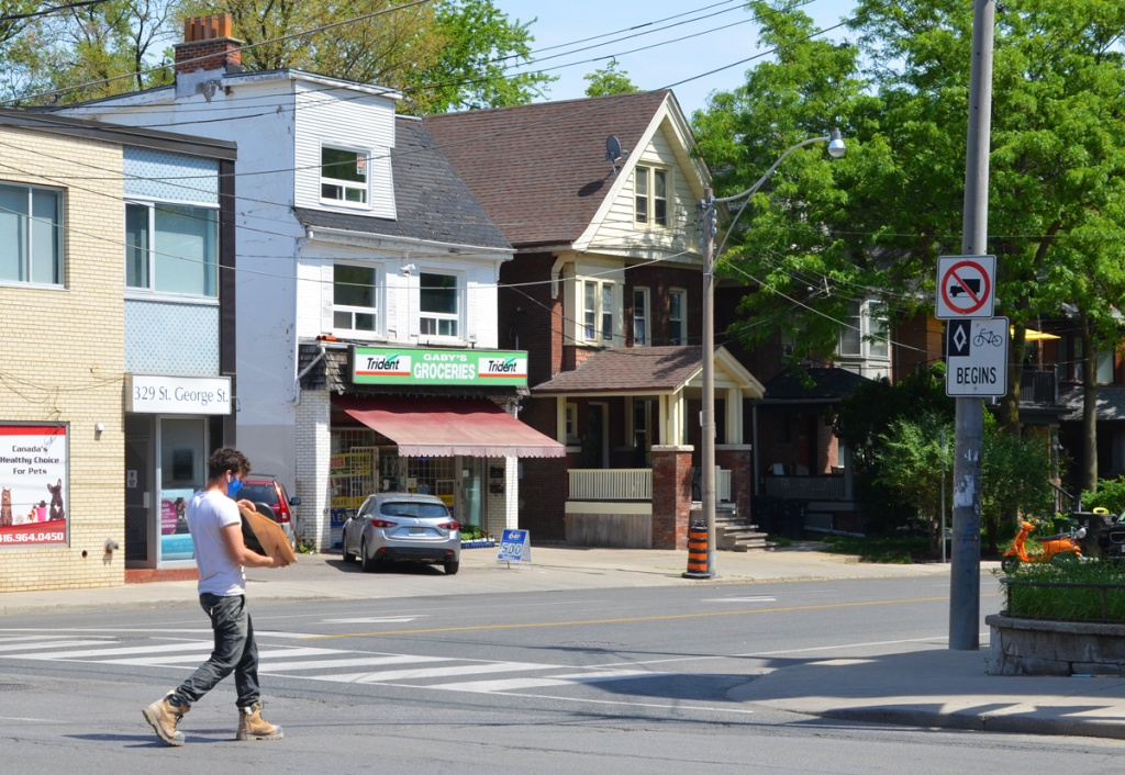 a man crosses Dupont near the intersection with St. George Street, Gabys Groceries is in the background with its green Trident gum advertisement sign