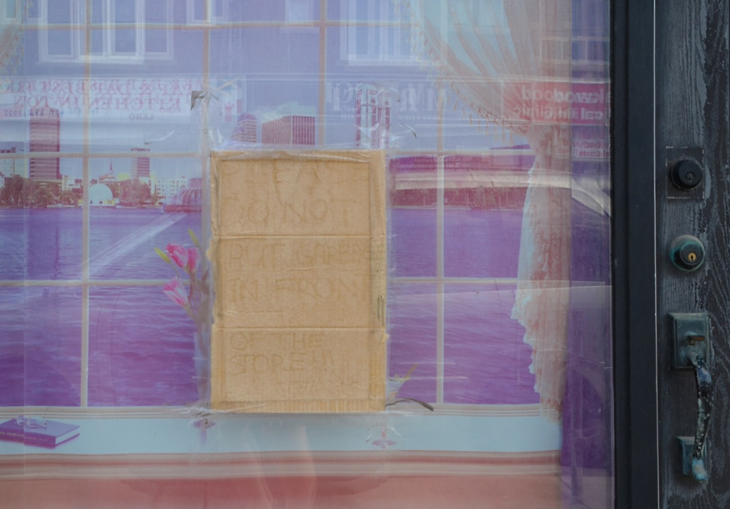 A purple picture in the window of a door with a cardboard sign in middle that says Please do not put garbage in front of the store, reflections of stores across the street in the window as well