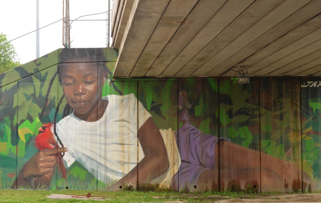mural by Jarus of a young girl holding a cardinal bird, beside sidewalk on TTC subway underpass Pharmacy Ave in Scarborough