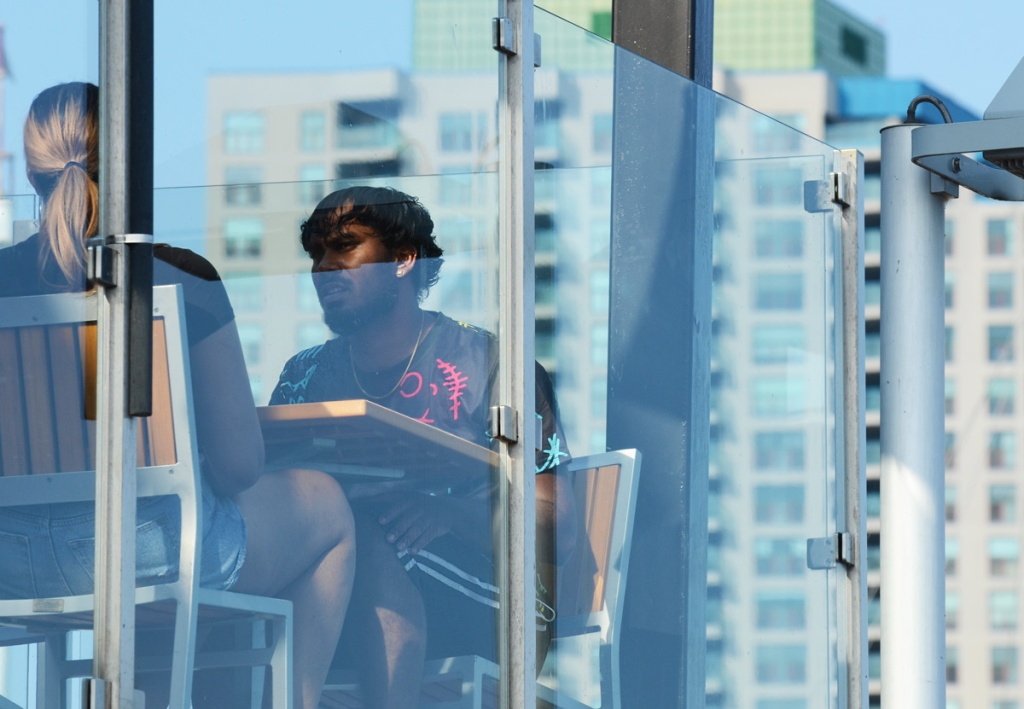 A couple sits at a table on an upper level balcony patio, behind glass barrier.  With condo buildings behind