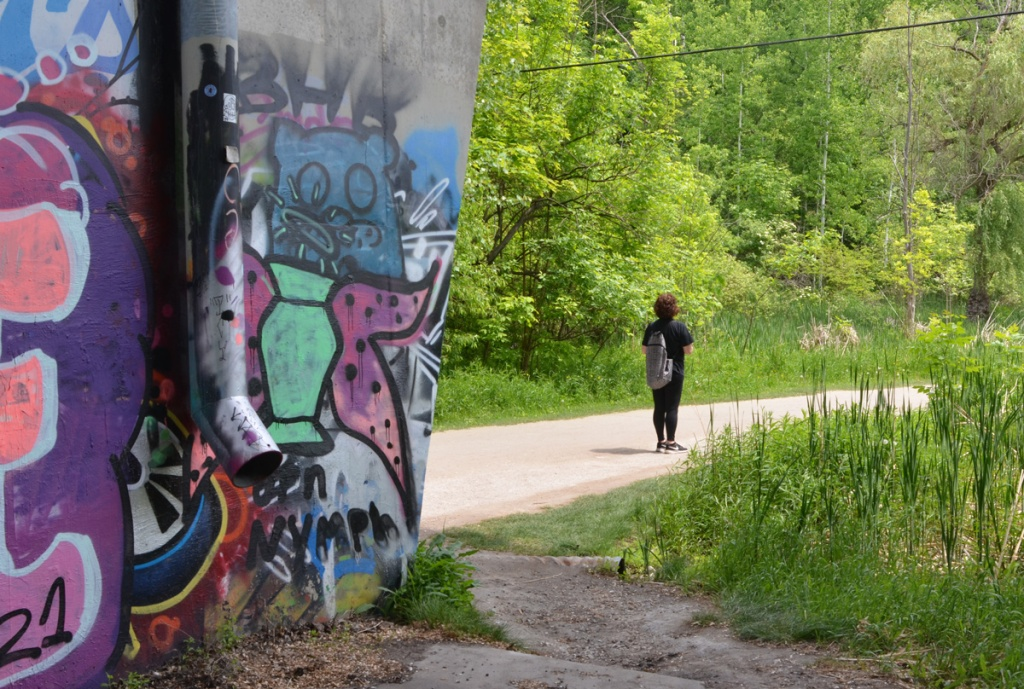woman walking on path in ravine park, with graffiti on wall behind her
