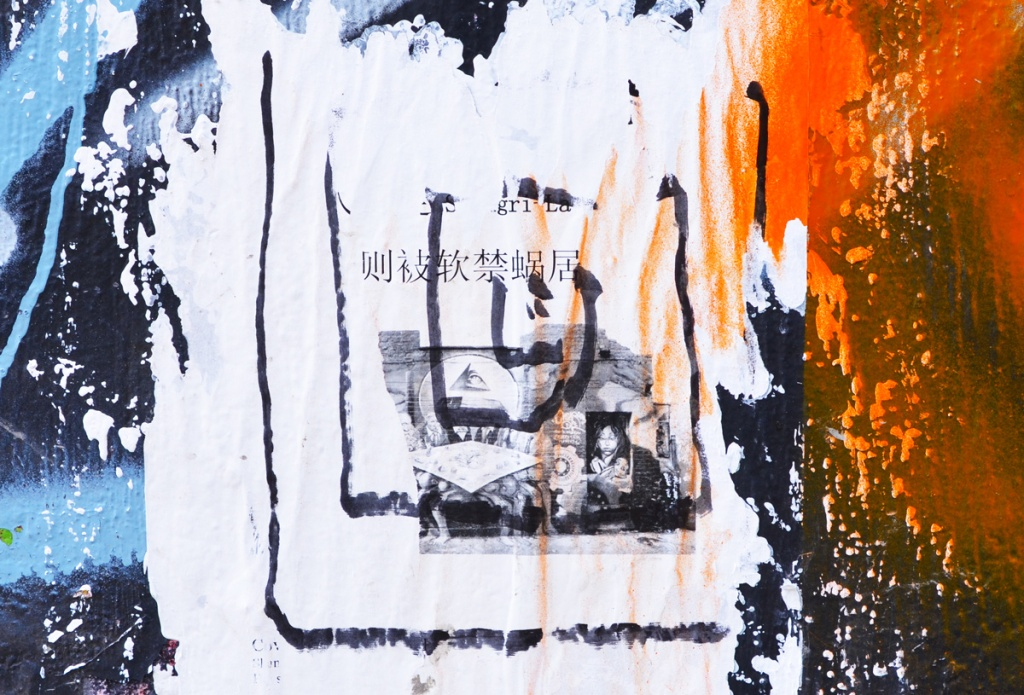paper paste up graffiti on a concrete pole with chinese lettering and black and white photos on it, orange and blue spray paint beside the paste up