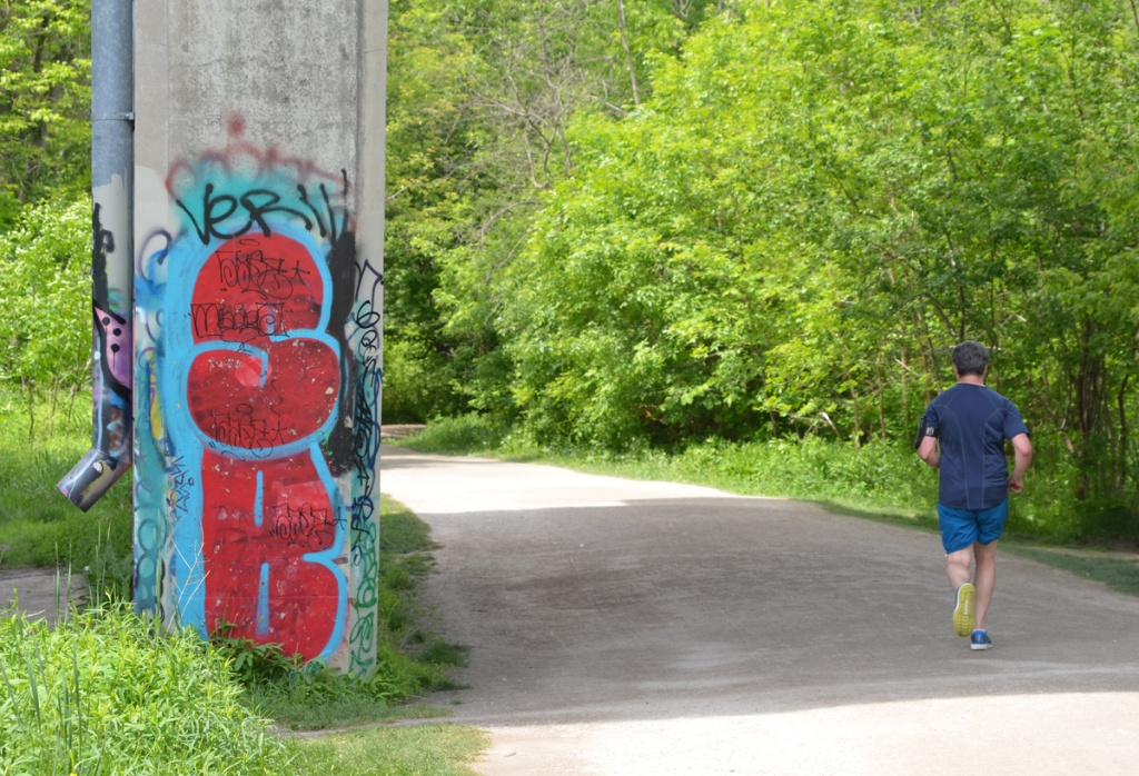 a man in blue top and shorts runs on a path under a bridge ,  support of bridge has graffiti on it, large red s and b on blue background