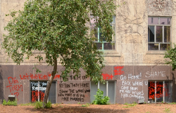 place where statue of Egerton Ryerson once stood, a single tree, graffiti on the walls of the building
