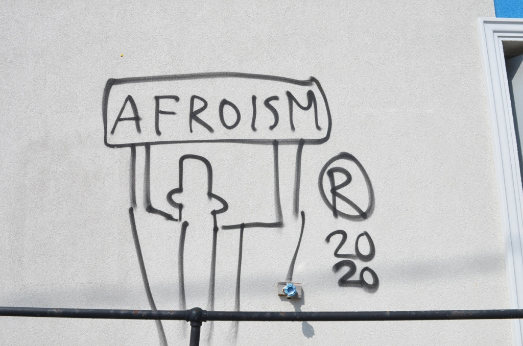 graffiti, black spray paint on a light grey concrete wall, outline of a person holding up a sign above head that says Afroism, 2020