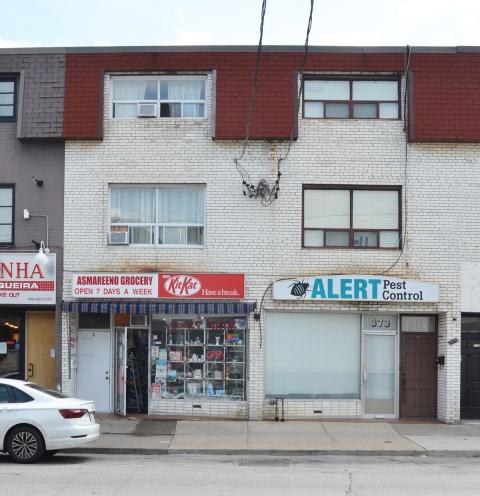 three storey white brick building with reddish mansard roof, lower floor is Asmareeno Grocery and Alert Pest Control