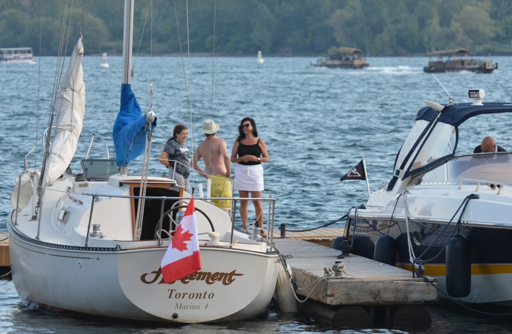 On Toronto waterfront, harbour, three people standing on the dock beside a sailboat, a man in yellow shorts and white hat, and two women.  A man is standing in the boat next to it.