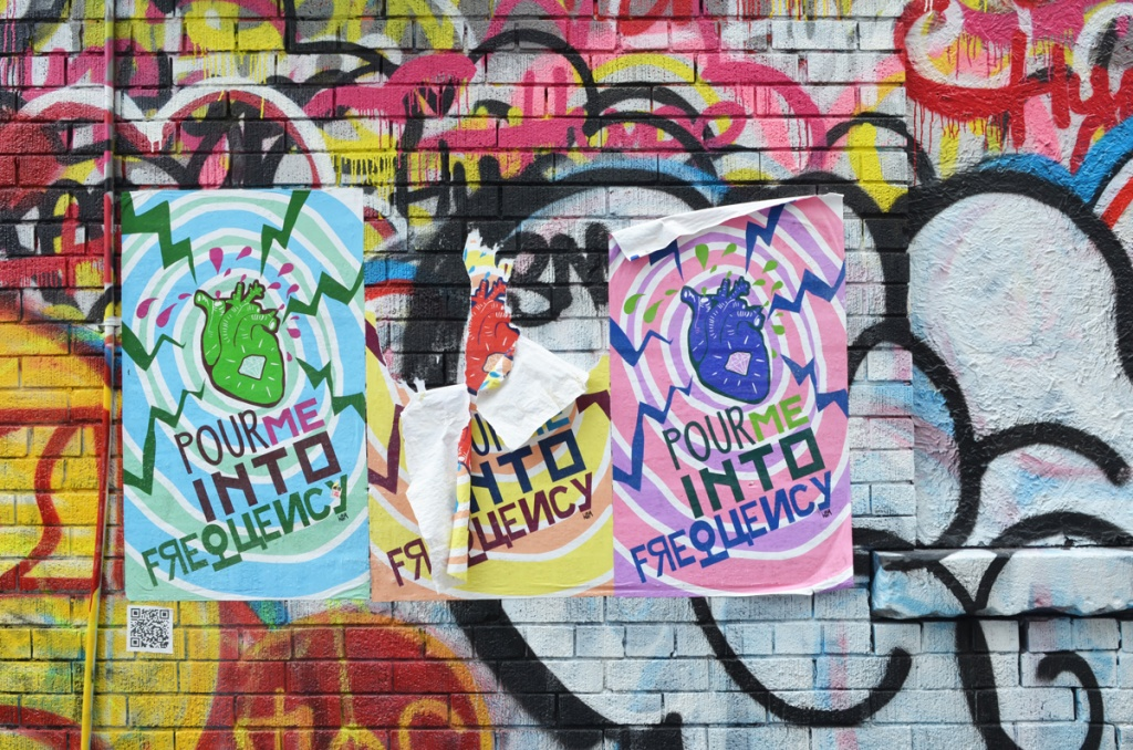 3 large graffiti posters in an alley, covering other street art, each with an anatomically correct heart in different colours (red, green and blue), and the words pour me into frequency