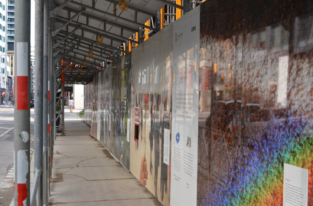 hoardings on Peter street, with covered walkway on sidewalk, photo exhibit on the hoardings