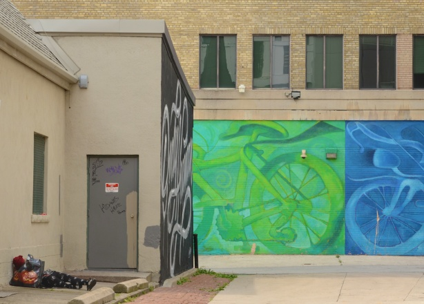 alley behind Ryerson Image Centre with large murals of green bike and blue bike, also with a person asleep in the alley by the church