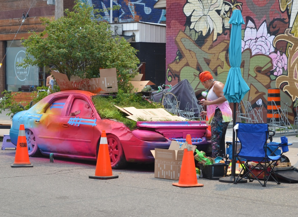 woman wearing an orange turban-like hat is painting a car in many bright colours, the car is full of plants growing inside it