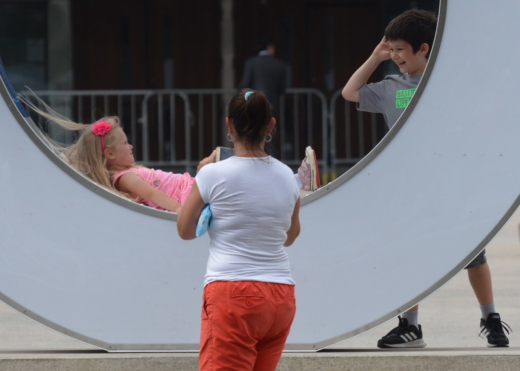a young boy teases his sister as she is lying in the center of the O of the Toronto 3 d sign, mother is taking a picture of daughter.  mother's back is to the camera