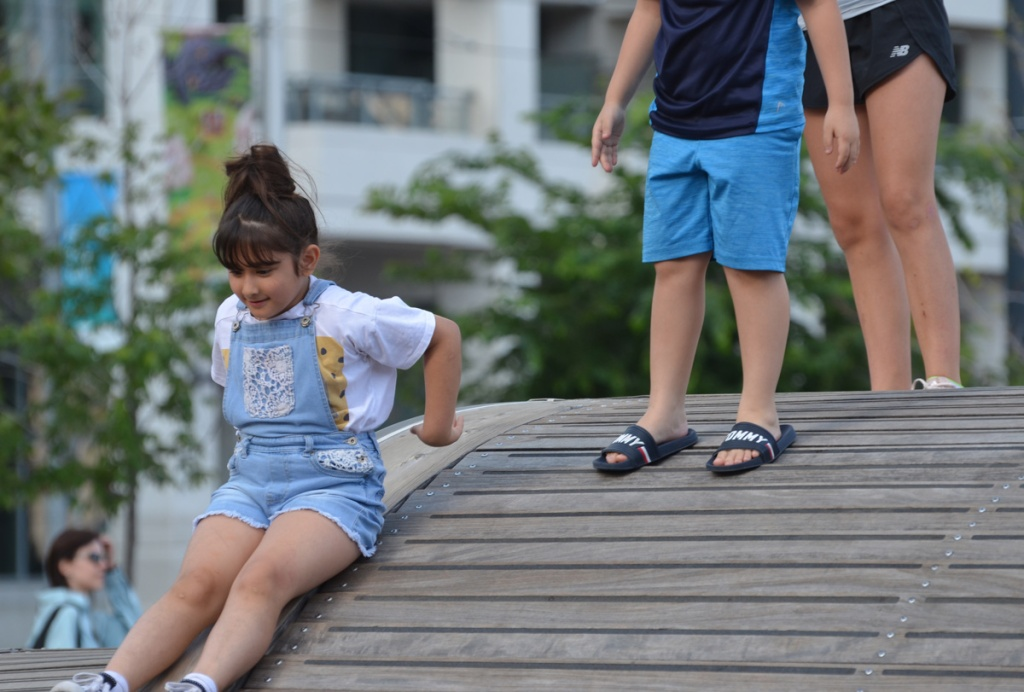 kids playing on the Simcoe Wave Deck, a young girl is sliding down it