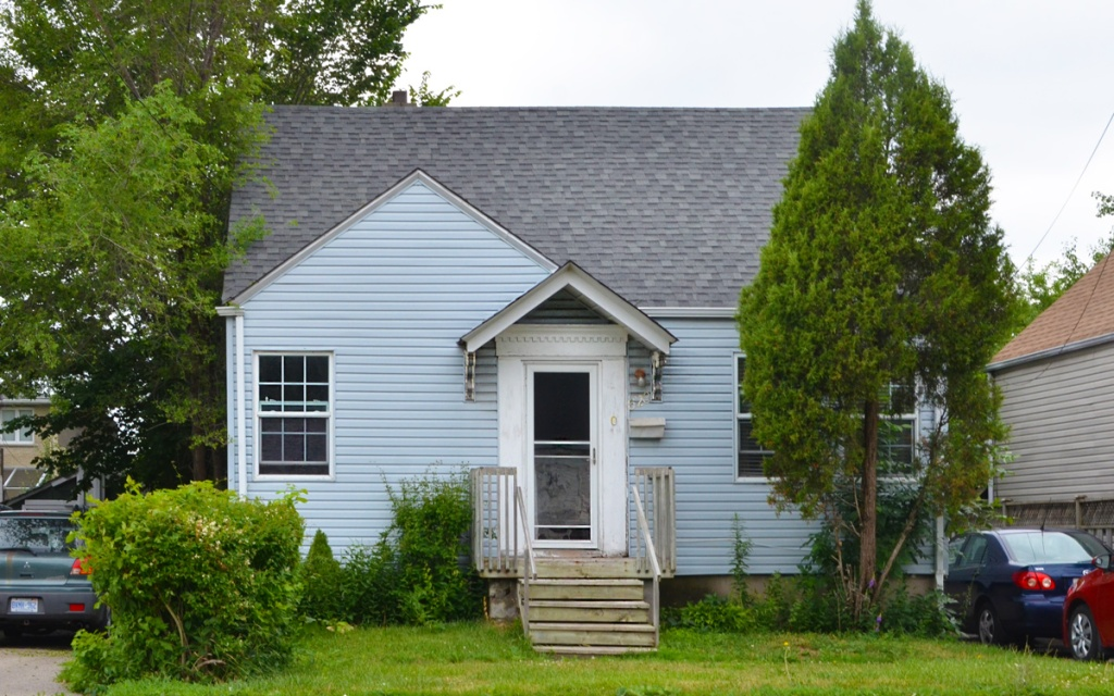 Little pale blue wood house with small porch and white front door