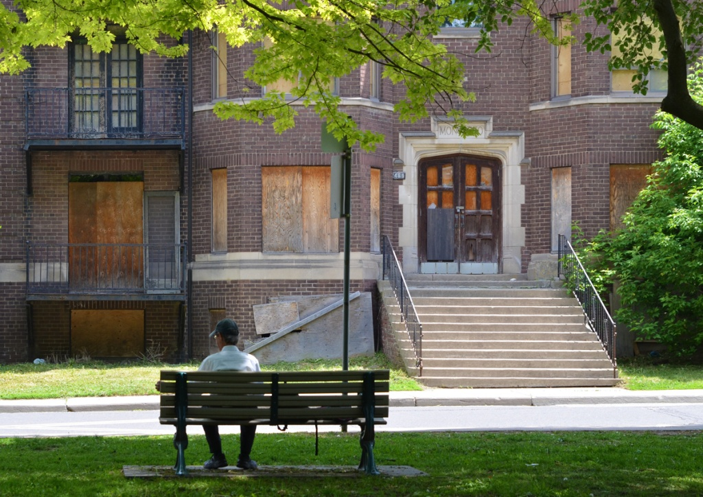 man sitting on a bench in a park with back to camera, looking across street to old boarded up brick apartment building