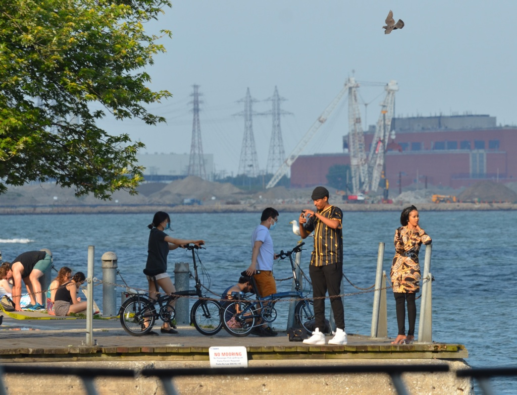 People by the side of Lake Ontario, two on bicycles, some sitting on the side of the walkway, a woman leaning against a post, and a man taking selfies.  There is also a seagull.   Port Lands is in the distance.