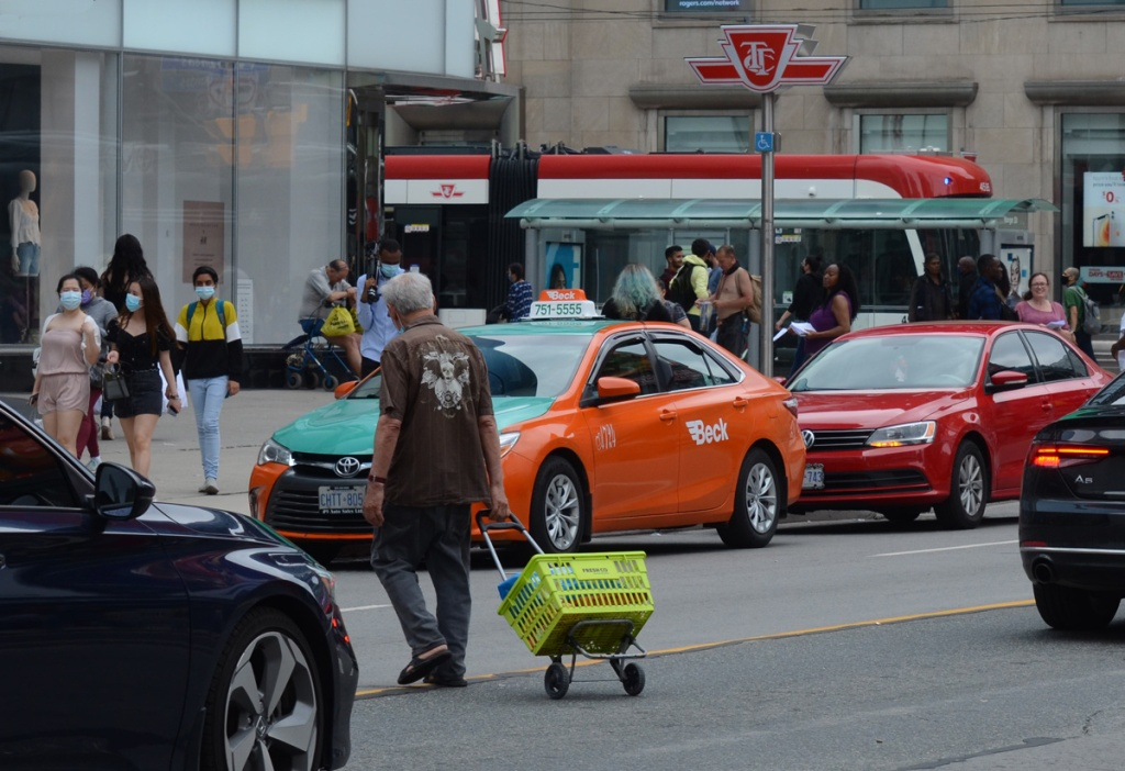 an older man in a brown shirt crosses Yonge street traffic while pulling a green basket on a dolly.  people in masks walking on the sidewalk, a Beck taxi parked on Yonge, a bare chested man by the bus stop, other people