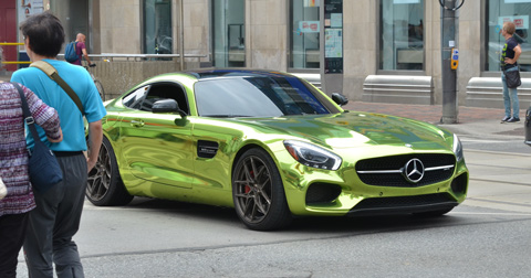 a very shiny metallic green mercedes sports car with no front licence passes through an intersection as a couple walk past