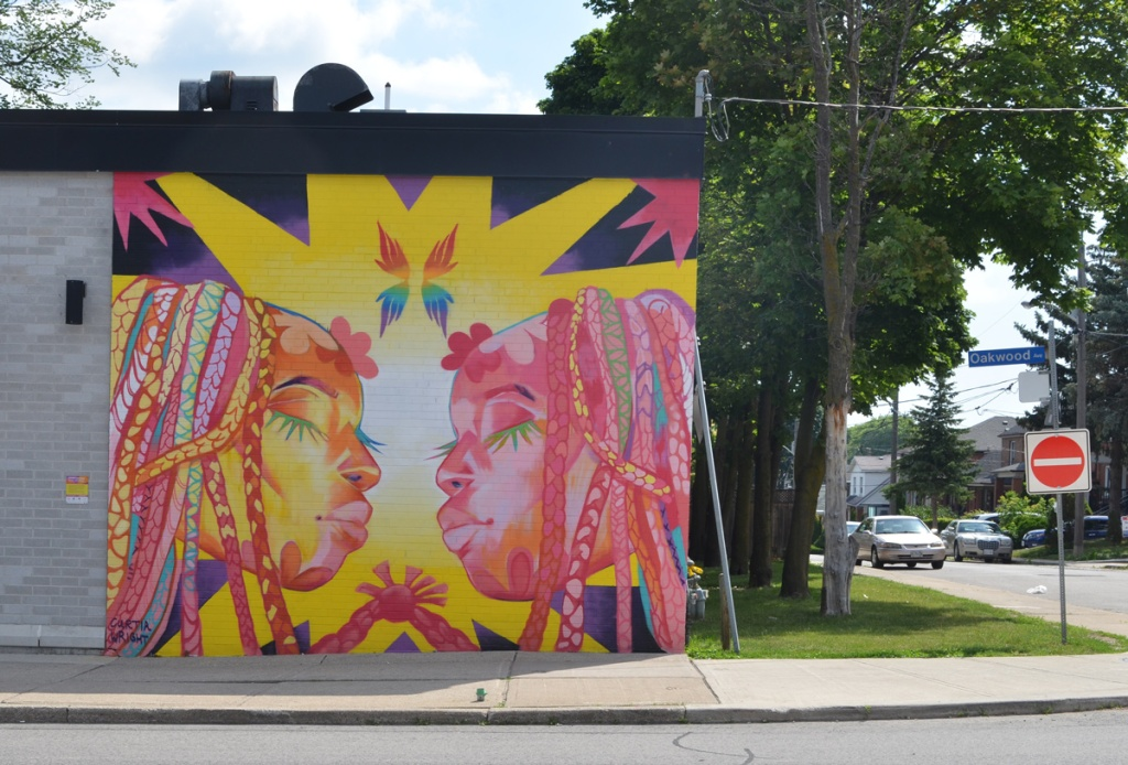 mural on the side of The Beer Store, in bright colours, two women with dreadlocks, eyes closed and about to kiss
