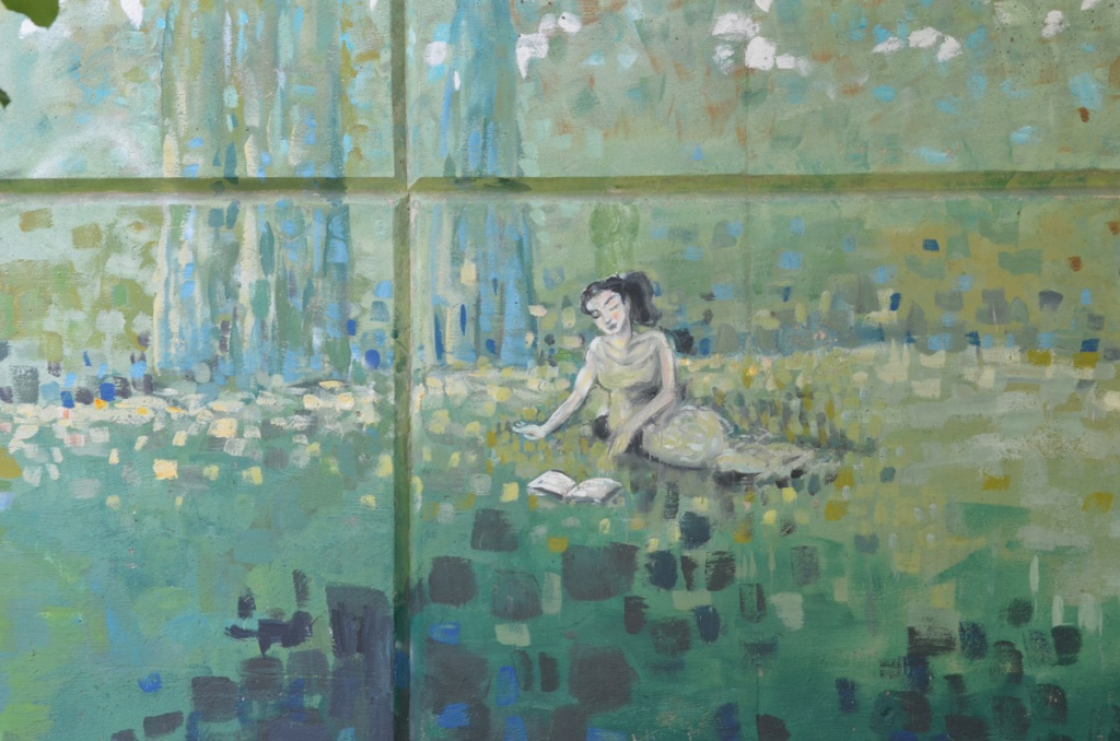 part of a mural on a concrete wall, a girl sitting on the grass and reading a book