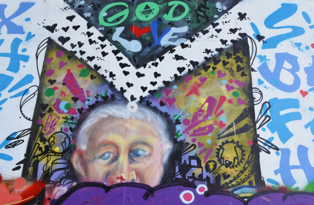 close up of old woman in mural, words god and love are written above her, some symbols beside her, lots of little hearts