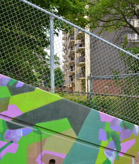 apartment building behind chainlink, triangular piece of mural in the foreground.