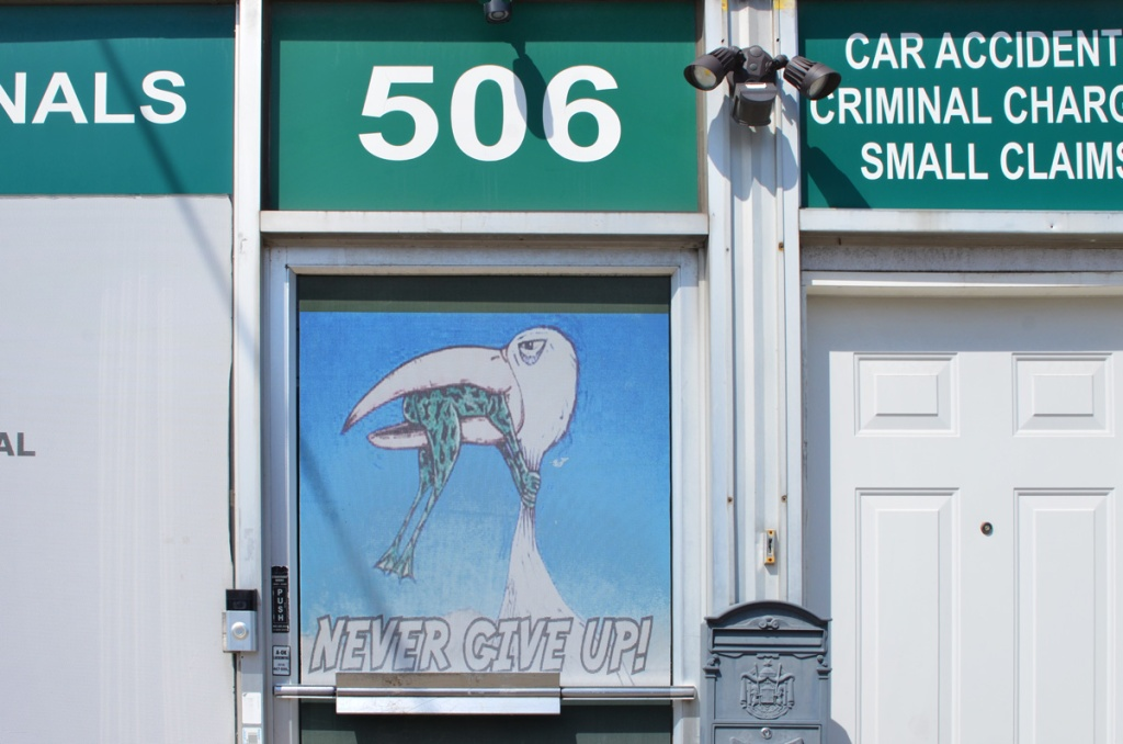 door with a window at 506 Oakwood, with a picture of a bird with a frog in its beak and the words Never give up
