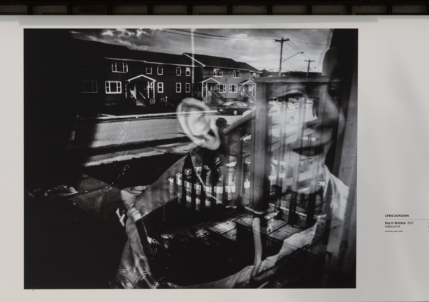a black and white photo by Chris Donovan with reflections of a boy in a window and street scene below, on display outside Ryerson Image Centre