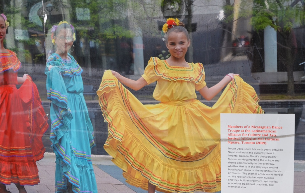 photograph on hoardings, three women of Nicaraguan dance troupe in long colourful dresses, red, yellow, and blue, also with flowers in their hair