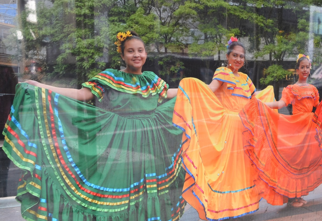 photograph on hoardings, three women of Nicaraguan dance troupe in long colourful dresses, green, yellow, and orange, also with flowers in their hair