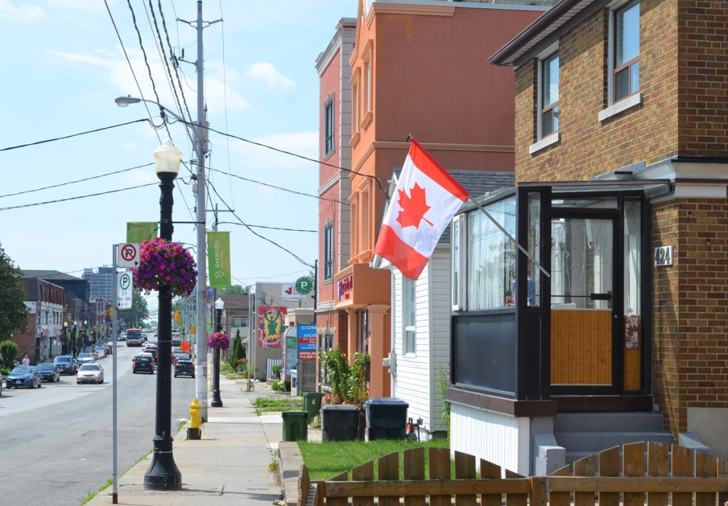 a house with a glassed in front porch and a Canadian flag flying outside the door, other stores and houses in the background