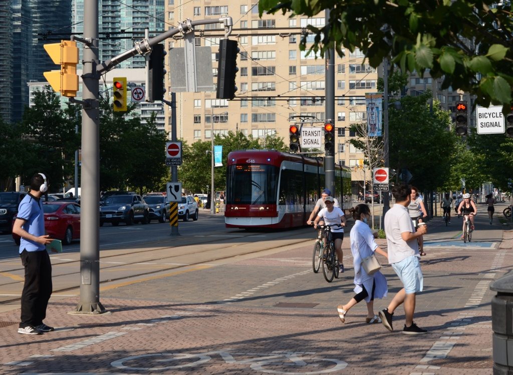 TTC street car on Queens Quay, cyclists on the bike path, pedestrians trying to cross