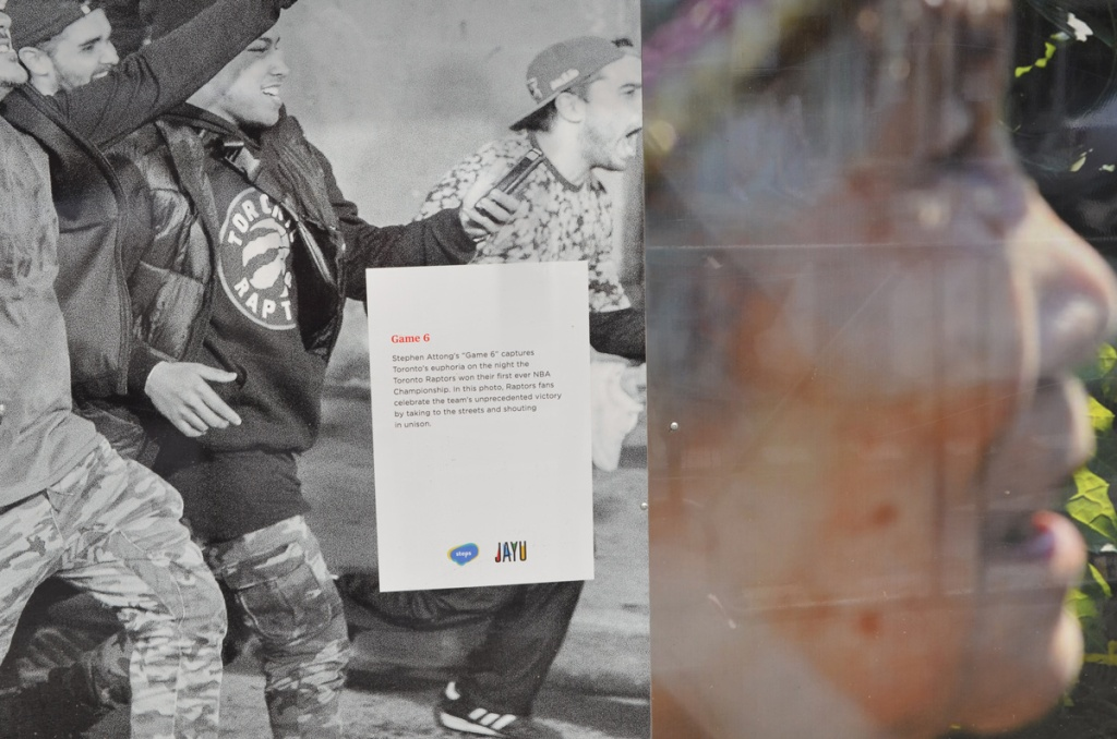 parts of two photos that are exhibited adjacent to each other on construction hoardings. on left is people at street party after Raptors won the NBA series and on the right is a close up of a woman's face in profile