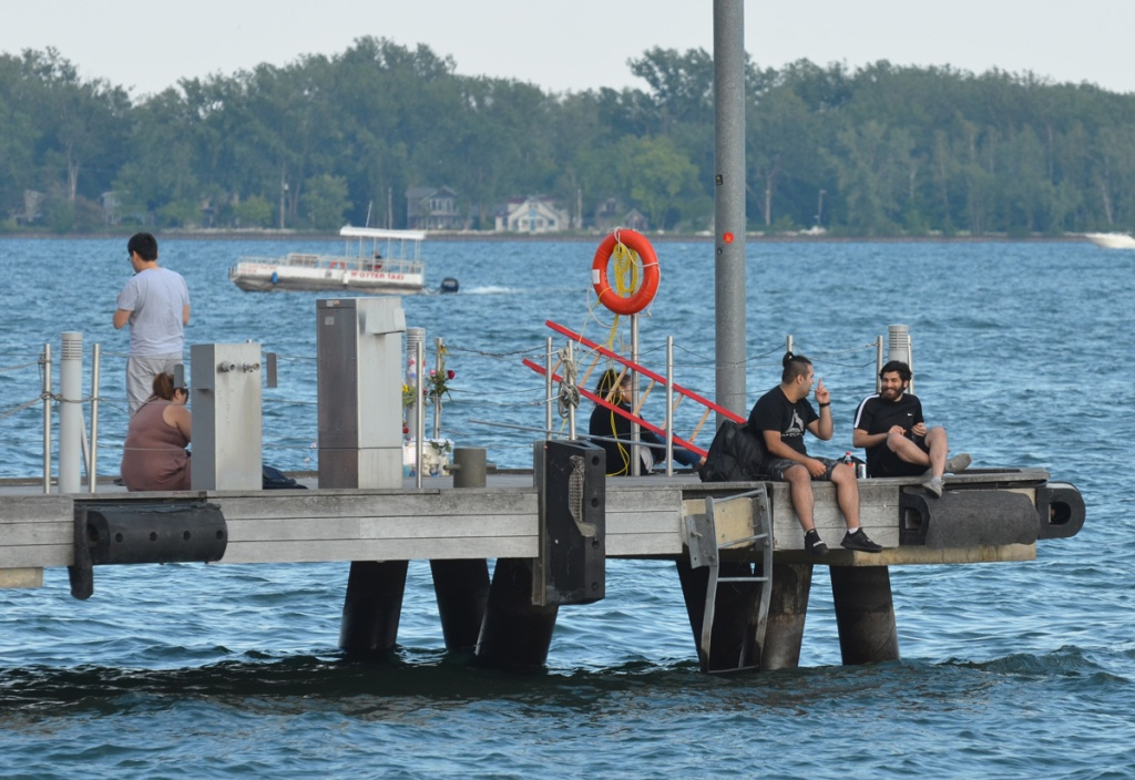people sitting on the end of a dock by Lake Ontario