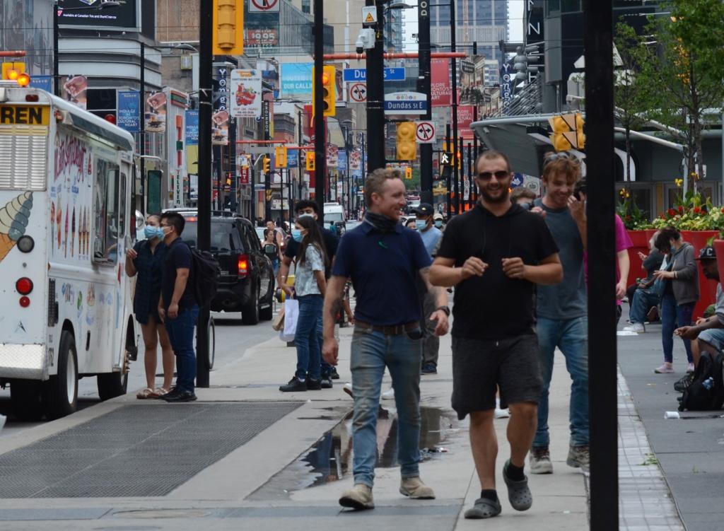 an Asian couple at the ice cream truck, men walking on the sidewalk, Yonge street at Dundas