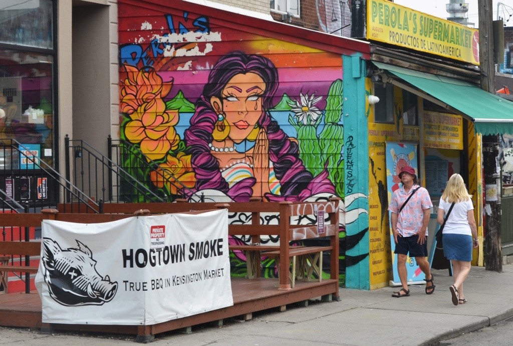 two people walking past a mural of a South American woman on Perolas Supermarket exterior  wall