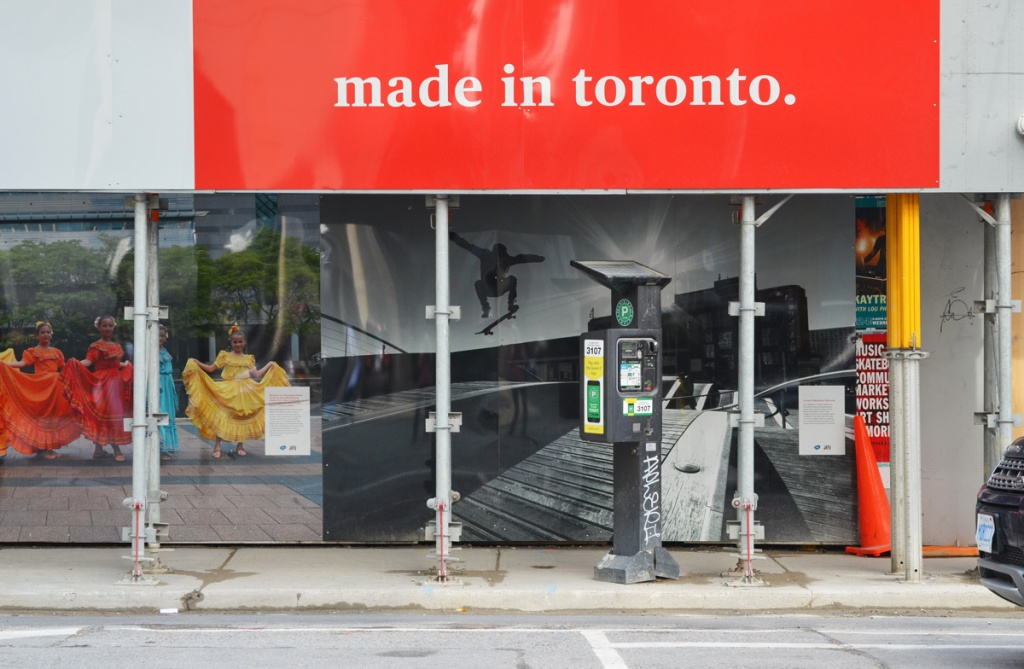 hoardings at a construction site, large red and white sign on top that says made in Toronto, a parking meter machine on the sidewalk, two large photographs on the hoardings, part of an exhibit