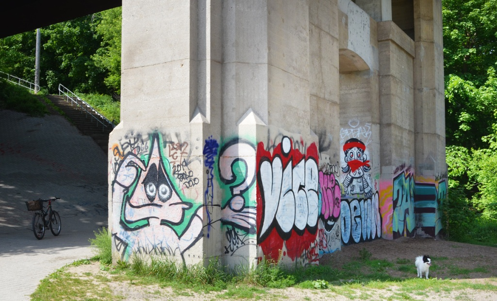a small black and white dog stands beside graffiti on the bottom part of a bridge support. triangle headed man holding a big question mark, the word vice, a man with red head band and red bandana over lower part of face,