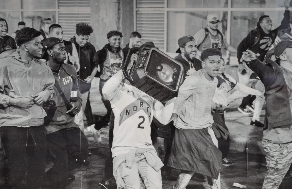 black and white image of Raptors victory party on the streets of Toronto, on hoardings