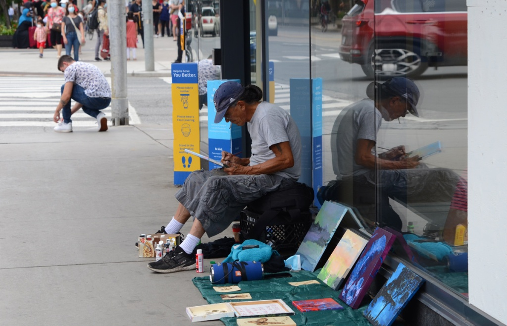 a man is drawing while sitting on the sidewalk, he has paintings and other artwork for sale,  his reflection is in the window behind him.  another man stops at the intersection to tie his shoe laces while waiting for the red light to turn green.  Dundas Street